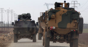 Turkish military vehicles drive in the Syrian rebel-held town of al-Rai, as they head towards the northern Syrian town of al-Bab