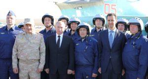 Hmejmími légitámaszpont, 2017. december 11. Vlagyimir Putyin orosz elnök (b4), Szergej Sojgu orosz védelmi miniszter (b2) és Bassár el-Aszad szíriai elnök (j3) pilótákkal fényképezkedik a szíriai Hmejmímnél működő orosz légitámaszponton 2017. december 11-én. Putyin a bázison tett villámlátogatásán elrendelte az orosz csapatok Szíriából történő visszavonásának megkezdését. (MTI/AP/Szputnyik/Kreml pool/Mihail Klimentyev)